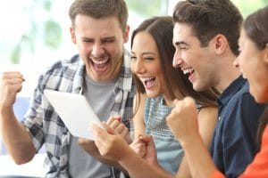 Excited group of friends watching tv from tablet